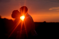 Bride and Groom kissing, silhouetted by the Iowa sunset